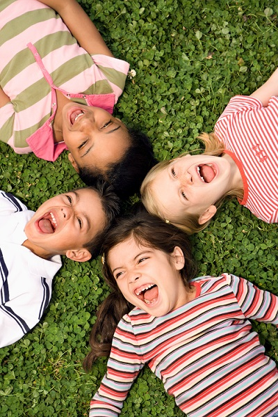 Children lying down on the ground smiling