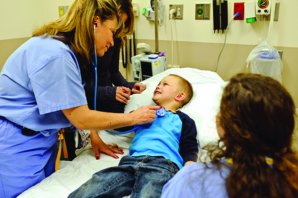 Nurse using stethiscope to hear childs heart