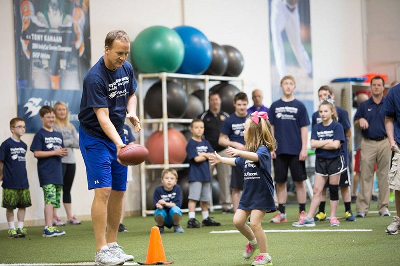 Peyton Manning tossing a football to a young girl at sports camp