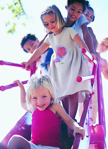 A group of children on a slide waiting in line