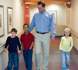 Peyton Manning walking down the hospital hallway with children