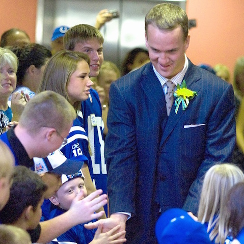 Peyton Manning greeting a group of young people.