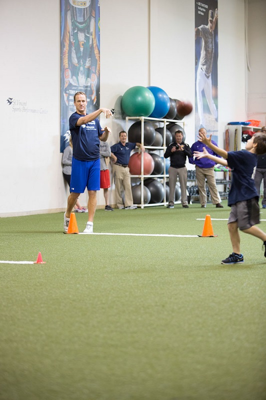 Peyton Manning throwing a football to a child at a sports camp