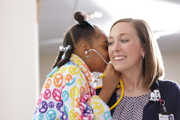 child wearing a stethoscope with a doctor