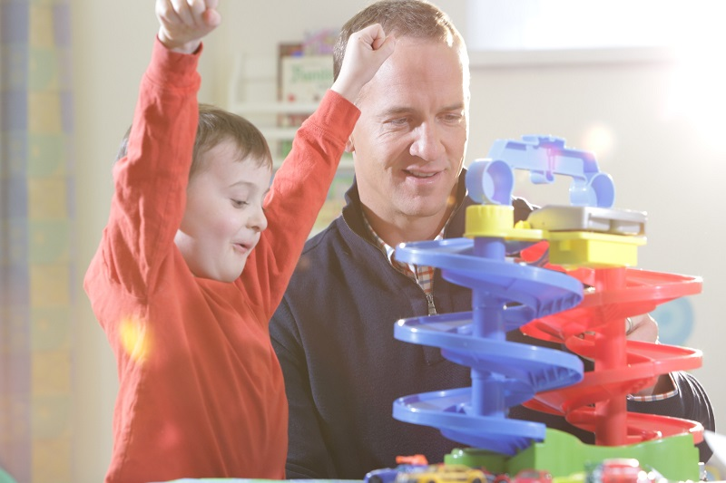 Peyton Manning playing with a child with toys