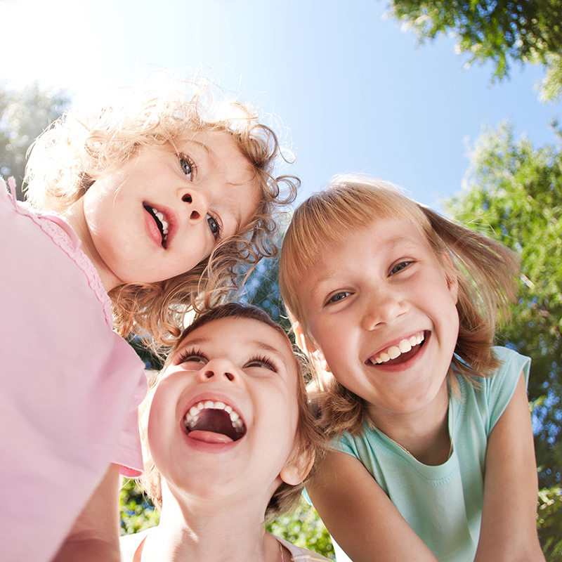 Three kids smiling and playing