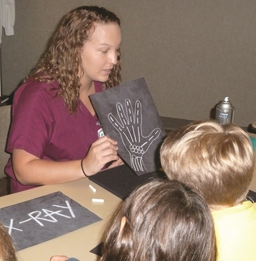 Nurse showing a hand drawn skeleton to a child
